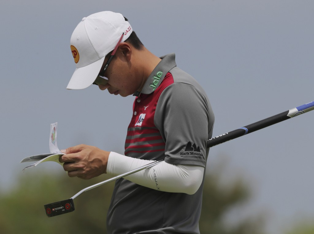 Jazz Janewattananond, of Thailand, checks his notes before putting on the 12th green during the second round of the PGA Championship golf tournament,