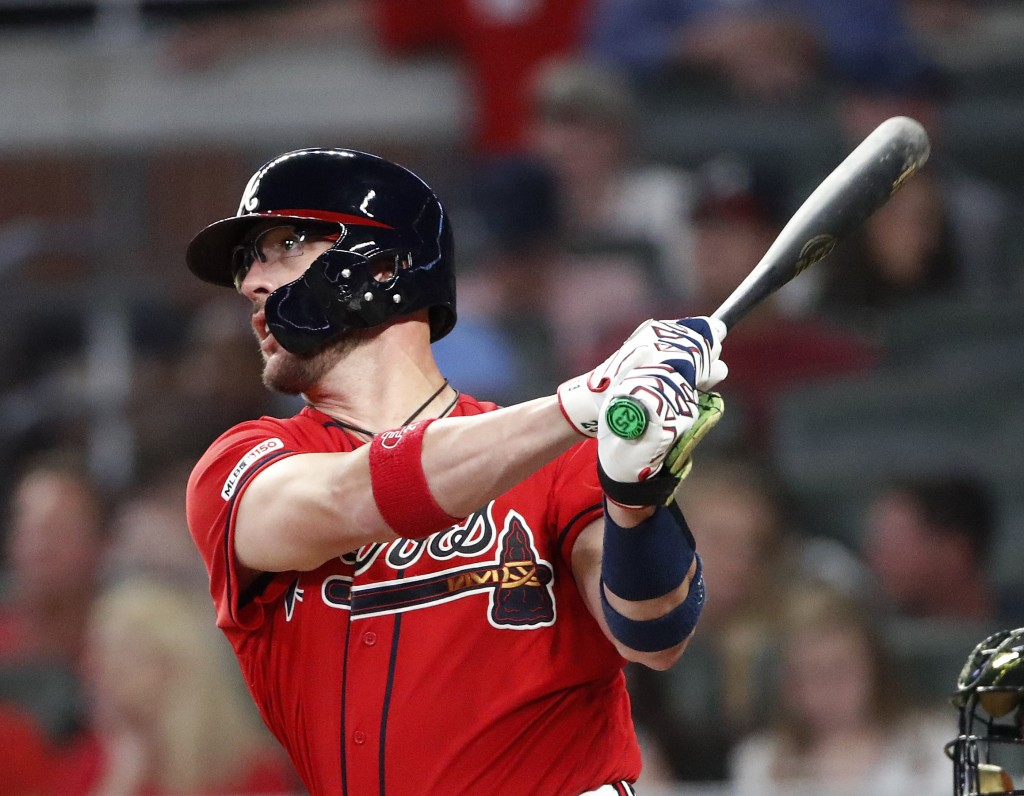 Atlanta Braves' Tyler Flowers follows through on a home run during the sixth inning of the team's baseball game against the Milwaukee Brewers on Frida
