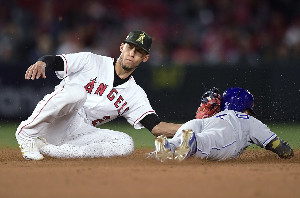 Kansas City Royals' Whit Merrifield, right, is tagged out by Los Angeles Angels shortstop Andrelton Simmons as he tried to steal second during the fif