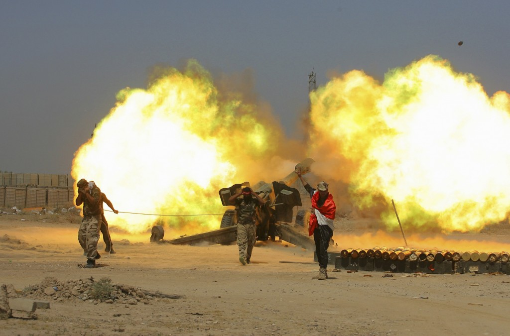FILE - In this May 29, 2016 file photo, Iraqi security forces and allied Popular Mobilization forces fire artillery during fight against Islamic State