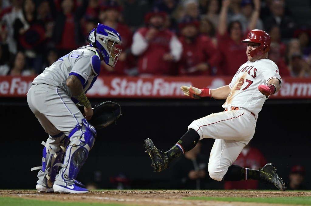 Los Angeles Angels' Mike Trout, right, scores on a single by Albert Pujols as Kansas City Royals catcher Martin Maldonado waits for the ball during th