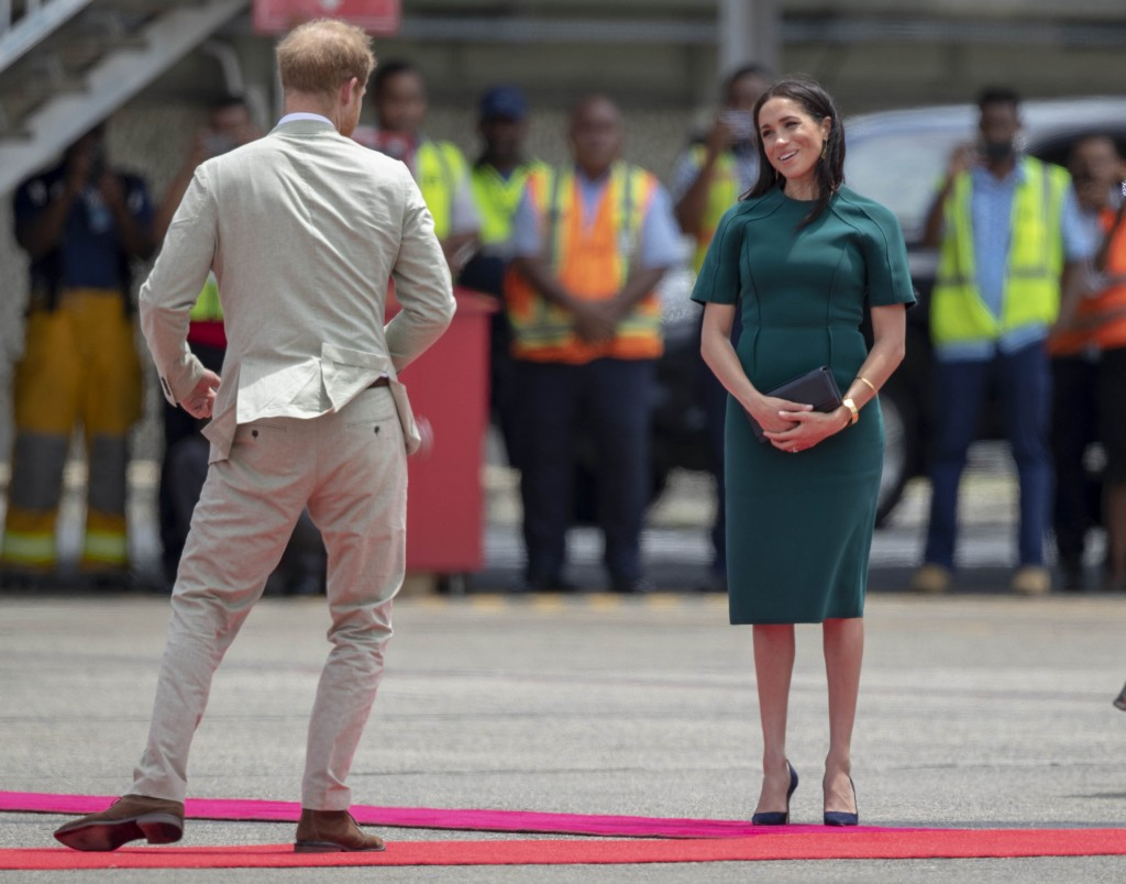 FILE - In this Thursday, Oct. 25, 2018 file photo, Britain's Prince Harry and Meghan, Duchess of Sussex react before boarding their flight from Nadi,
