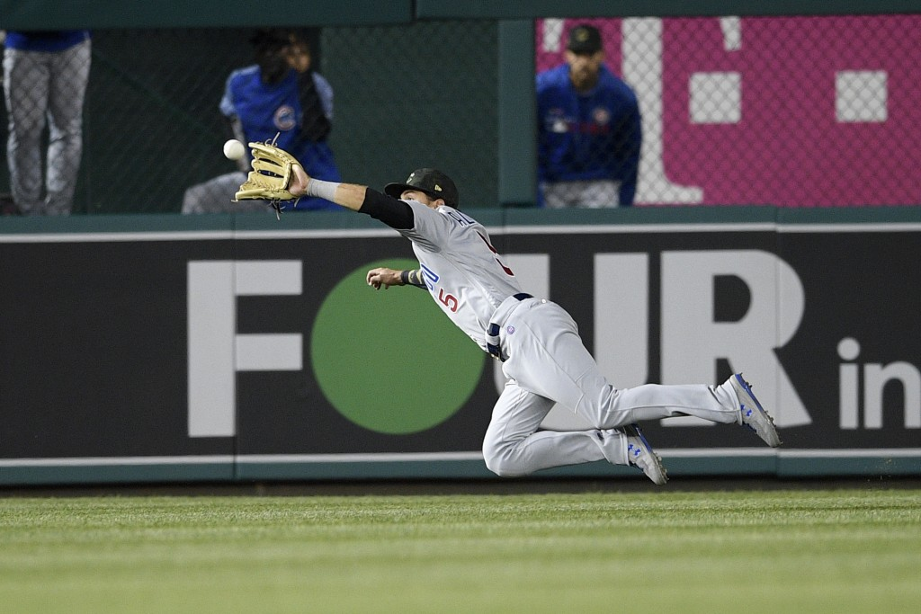 Chicago Cubs center fielder Albert Almora Jr. (5) dives for and catches a line drive by Washington Nationals' Juan Soto for an out during the ninth in