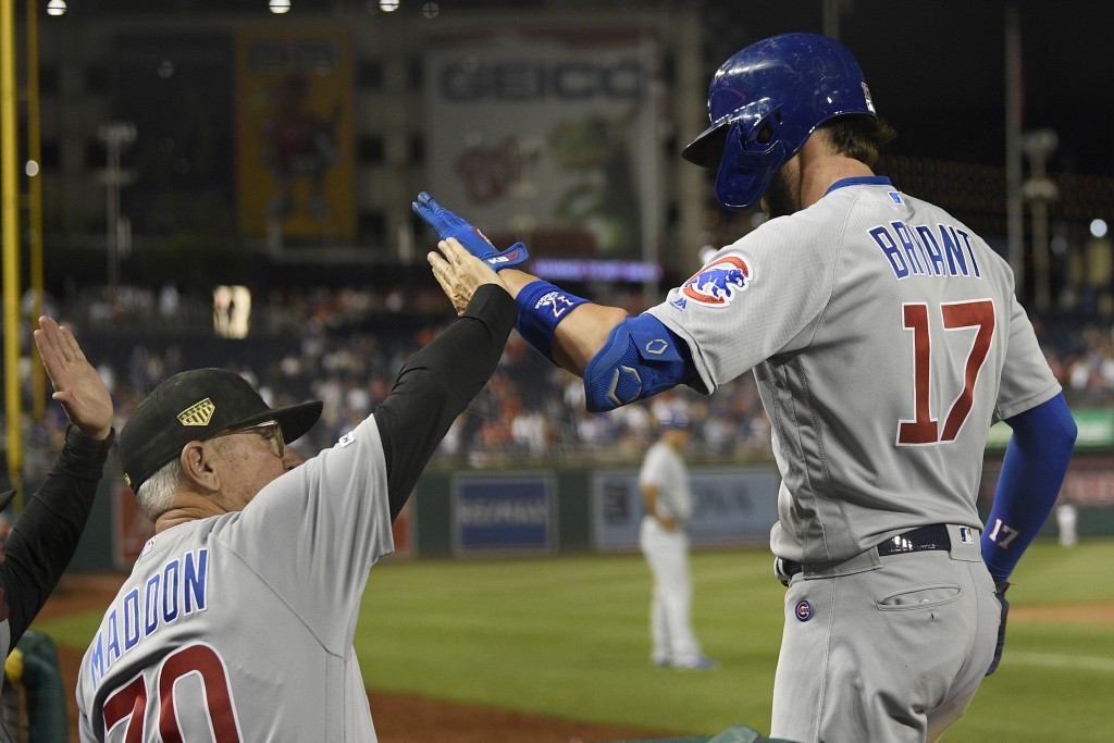 Chicago Cubs' Kris Bryant (17) celebrates his two-run home run with manager Joe Maddon (70) during the ninth inning of a baseball game against the Was...