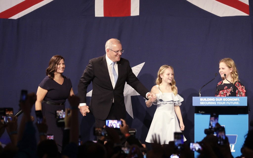 Australian Prime Minister Scott Morrison, second left, arrives on stage to speak to party supporters flanked by his wife, Jenny, left, and daughters L