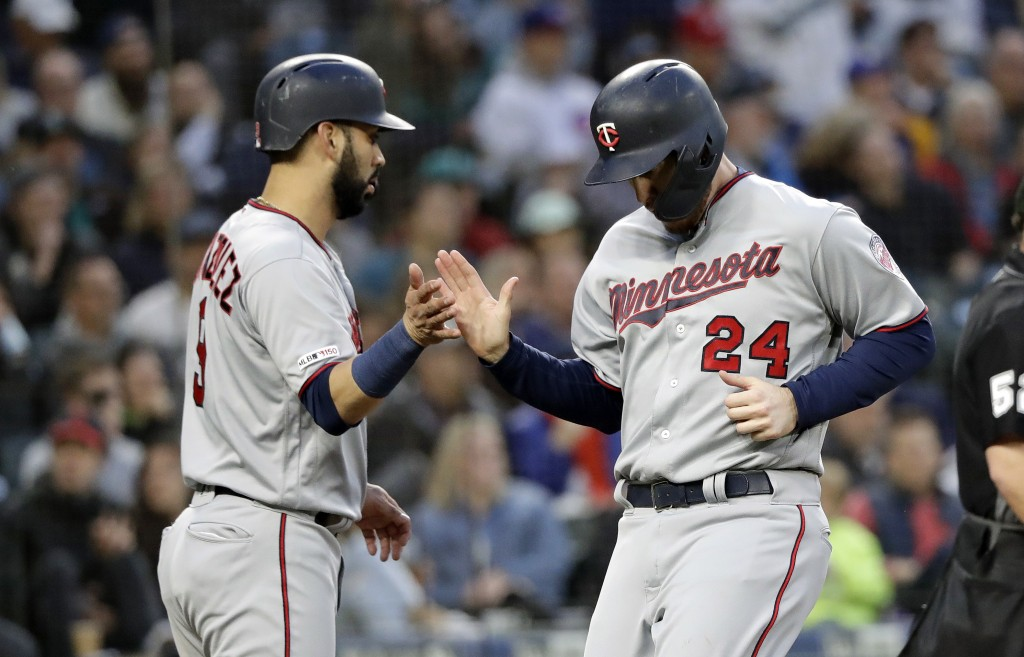 Minnesota Twins' Marwin Gonzalez greets C.J. Cron (24) after the two scored against the Seattle Mariners during the fifth inning of a baseball game Fr
