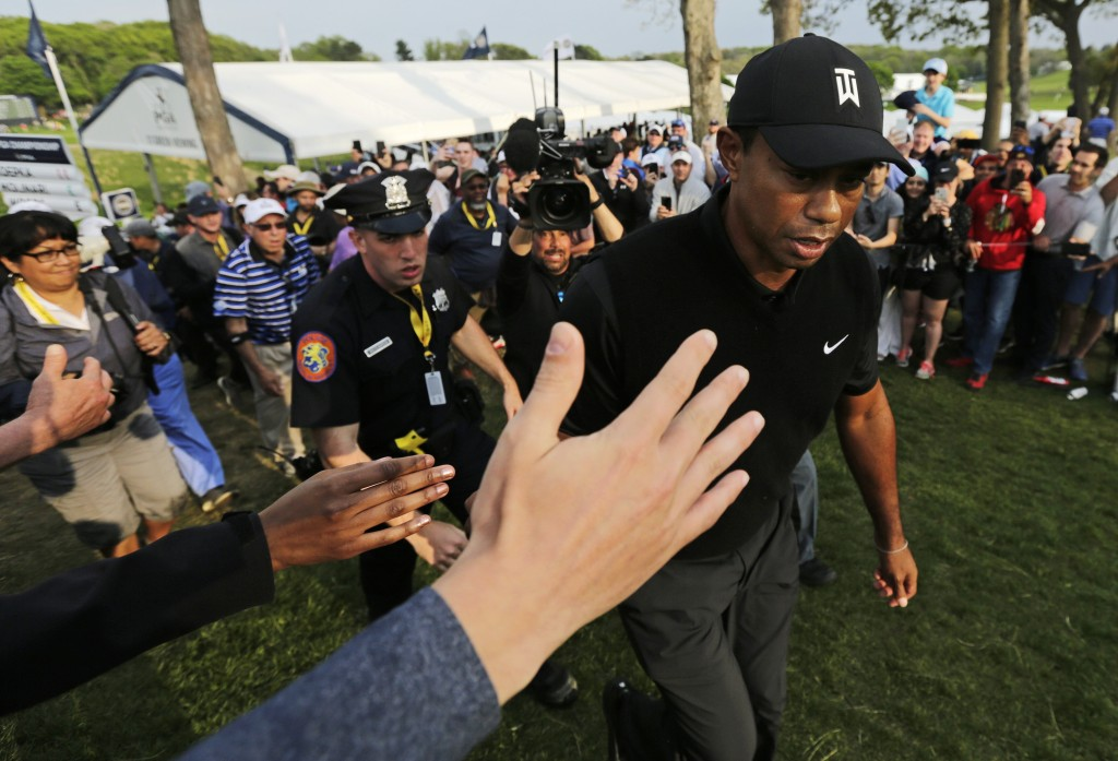 Golf fans reach out to Tiger Woods as he walks to the 18th tee during the second round of the PGA Championship golf tournament, Friday, May 17, 2019,