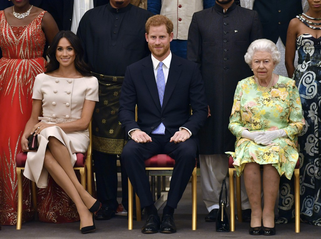 FILE - In this Tuesday, June 26, 2018 file photo, Britain's Queen Elizabeth, Prince Harry and Meghan, Duchess of Sussex pose for a group photo at the