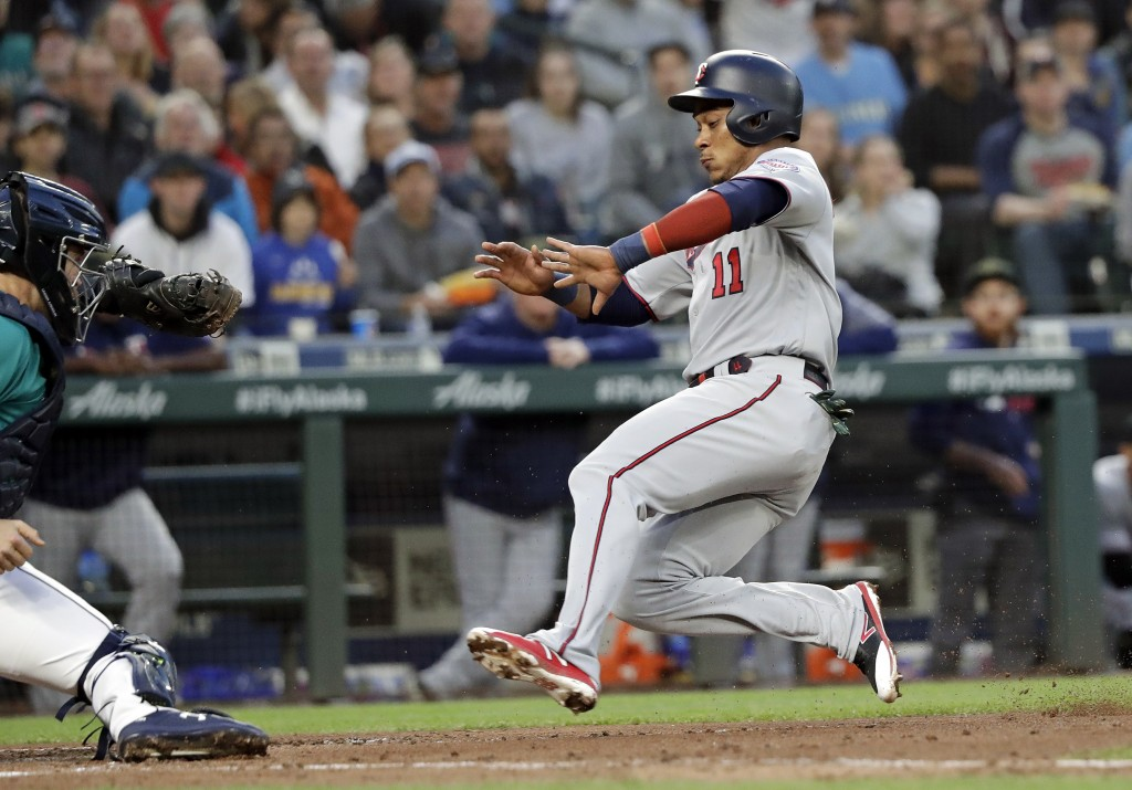 Minnesota Twins' Jorge Polanco (11) begins his slide home to score as Seattle Mariners catcher Tom Murphy readies a tag during the fifth inning of a b