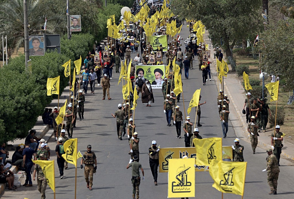 FILE - In this June 8, 2018 file photo, Iraqi Popular Mobilization Forces march as they hold their flag and posters of Iraqi and Iranian Shiites spiri
