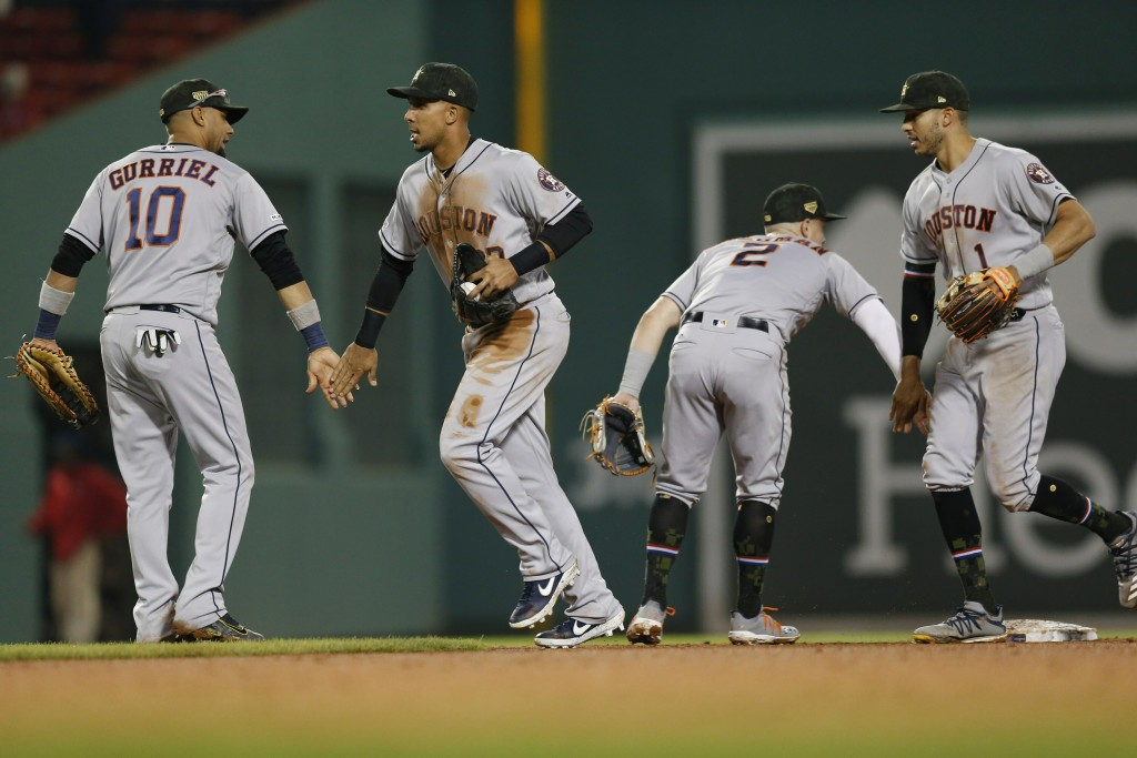 Houston Astros' Yuli Gurriel (10), Michael Brantley (23), Alex Bregman (2) and Carlos Correa (1) celebrate after the Astros defeated the Boston Red So