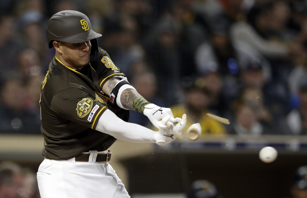 San Diego Padres' Manny Machado breaks his bat as he hits into a double play during the third inning of the team's baseball game against the Pittsburg