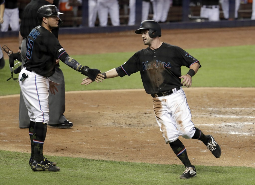 Miami Marlins' Miguel Rojas (19) and Jon Berti congratulate each other after scoring on a single by Garrett Cooper during the third inning of the team...