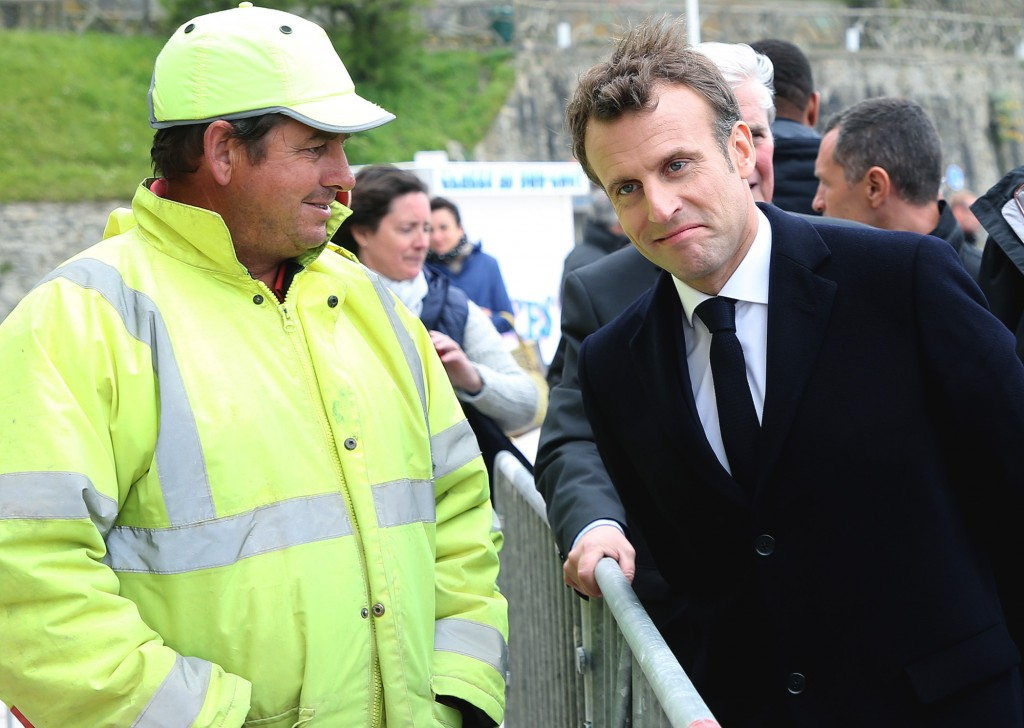France's President Emmanuel Macron, right, talks to a worker during a visit to Biarritz, southwestern France, Friday, May 17, 2019. (AP Photo/Bob Edme...