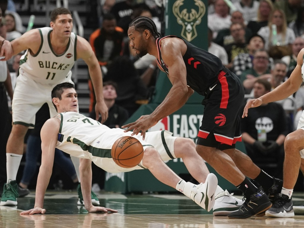 FILE - In this Wednesday, May 15, 2019, file photo, Toronto Raptors' Kawhi Leonard is called for a charge on Milwaukee Bucks' Ersan Ilyasova during th