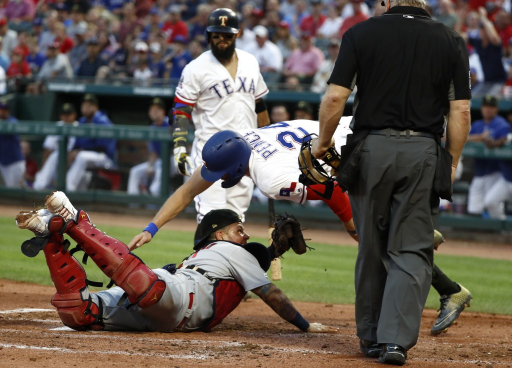 Home plate umpire Bill Miller, front right, watches as St. Louis Cardinals catcher Yadier Molina, bottom, prepares to tag out Texas Rangers' Hunter Pe
