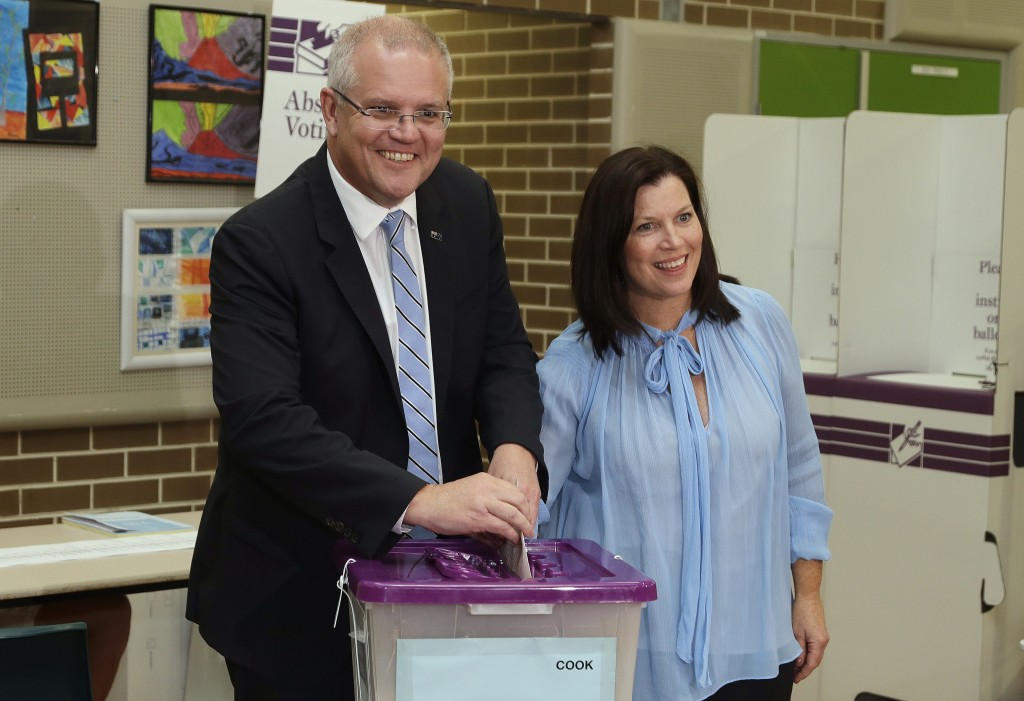 Australian Prime Minister Scott Morrison, left, is assisted by his wife, Jenny, as he casts his ballot in a federal election in Sydney, Australia, Sat