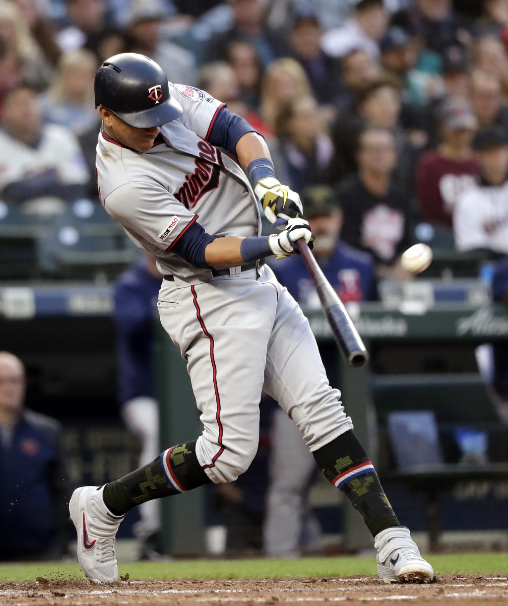 Minnesota Twins' Ehire Adrianza hits an RBI sacrifice fly against the Seattle Mariners during the fourth inning of a baseball game Friday, May 17, 201