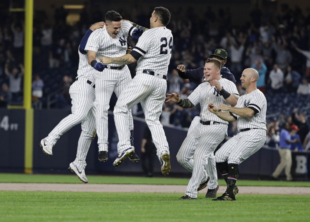 New York Yankees' Gio Urshela celebrates with teammates after hitting an RBI single during the ninth inning of the team's baseball game against the Ta