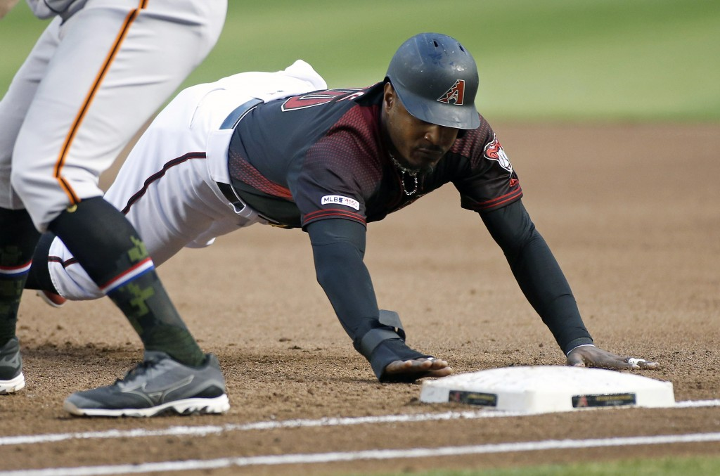 Arizona Diamondbacks' Adam Jones dives back to first base on a pickoff-attempt by the San Francisco Giants during the second inning of a baseball game