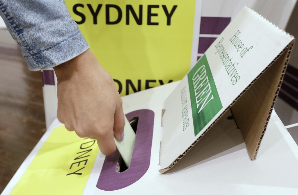 A voter casts their ballot at the Town Hall in Sydney, Australia, in a federal election, Saturday, May 18, 2019. Both major parties are promising that