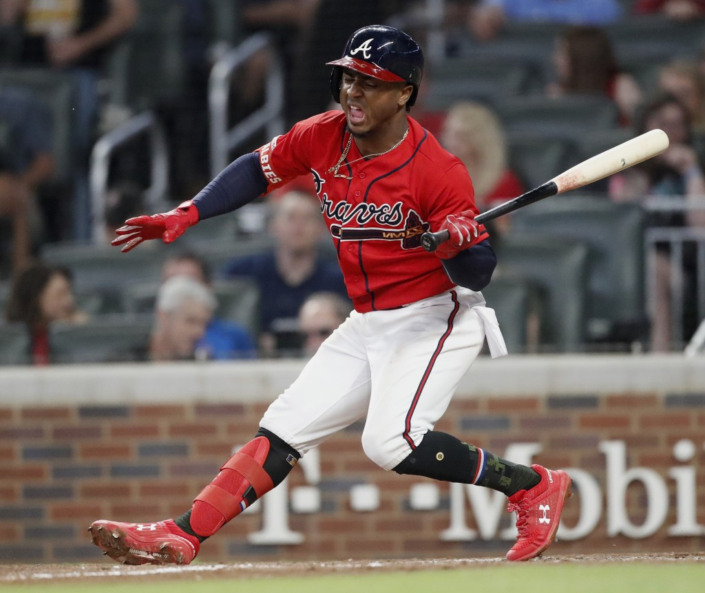 Atlanta Braves second baseman Ozzie Albies stumbles as he bats against the Milwaukee Brewers during the sixth inning of a baseball game Friday, May 17