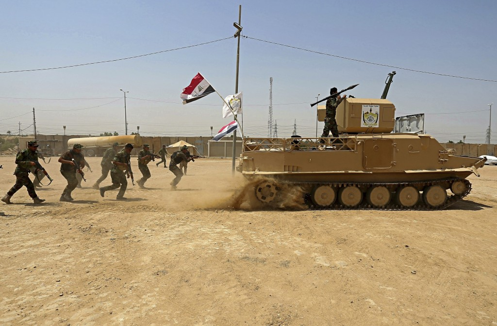 FILE - In this July 18, 2017 file photo, Shiite Volunteer fighters from the Imam Ali Brigade, an armed faction with the Iraqi Popular Mobilization For...