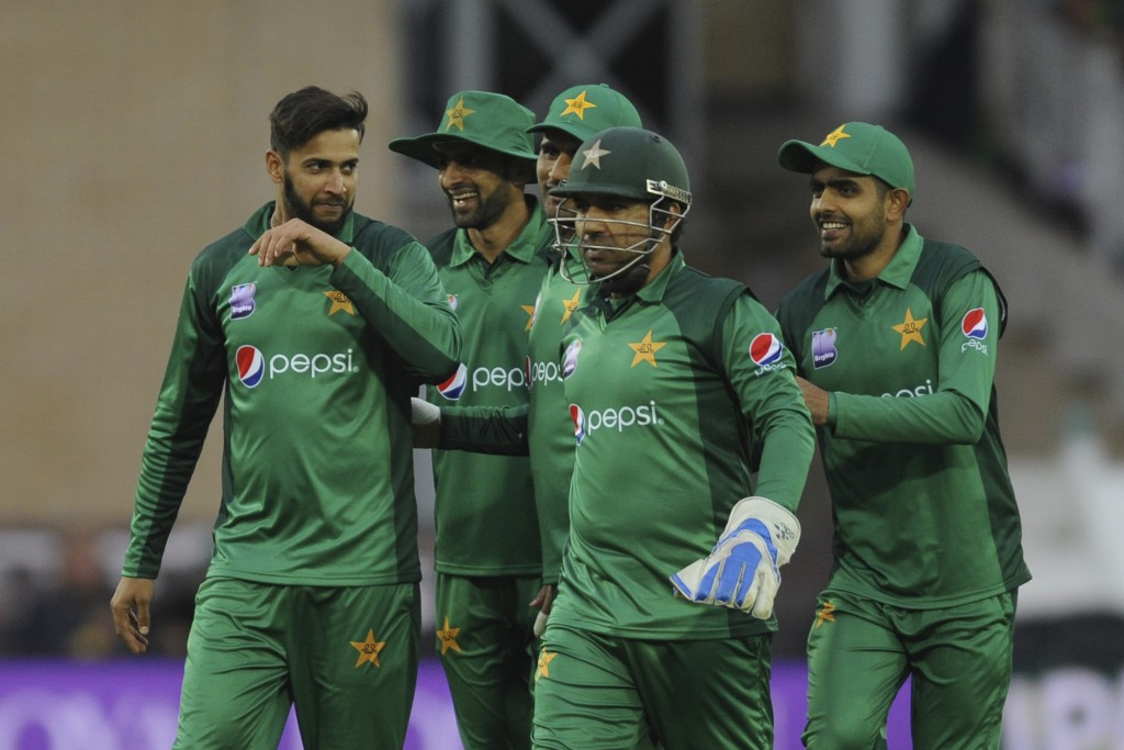 Pakistan's Imad Wasim, left, celebrates with his teammates taking the wicket of England's Jos Buttler during the Fourth One Day International cricket