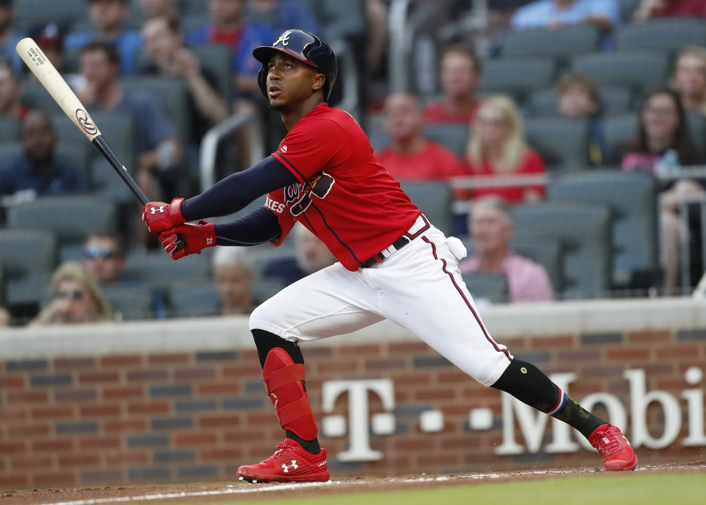 Atlanta Braves' Ozzie Albies watches his RBI sacrifice fly during the second inning of the team's baseball game against the Milwaukee Brewers on Frida