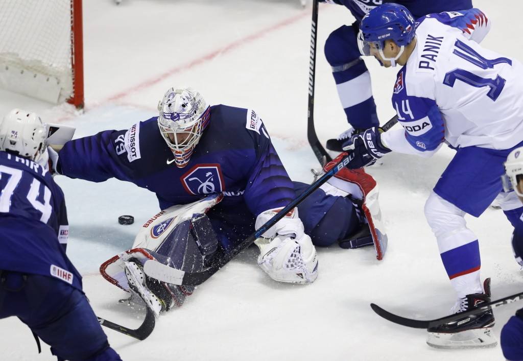 Goaltender Florian Hardy of France, center, stretches to make a save against Slovakia's Richard Panik, right, during the Ice Hockey World Championship