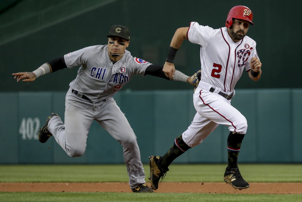 Washington Nationals' Adam Eaton (2) is tagged out by Chicago Cubs shortstop Javier Baez after trying to steal second during the third inning of a bas