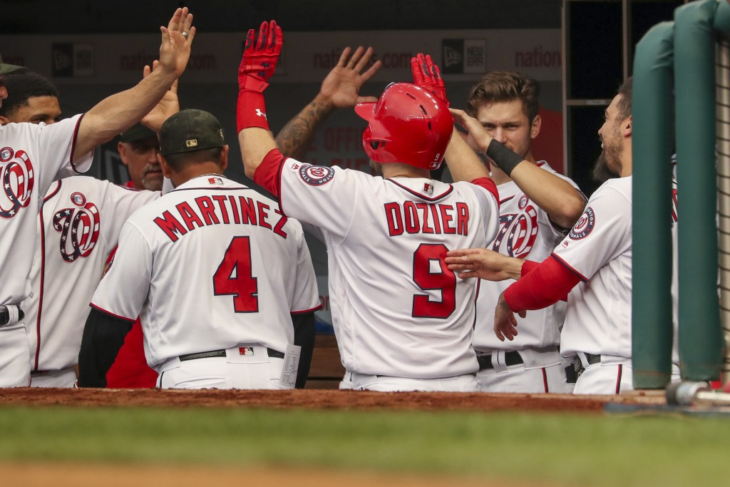 Washington Nationals' Brian Dozier (9) high-fives teammates after hitting a solo home run during the second inning of the team's baseball game against...