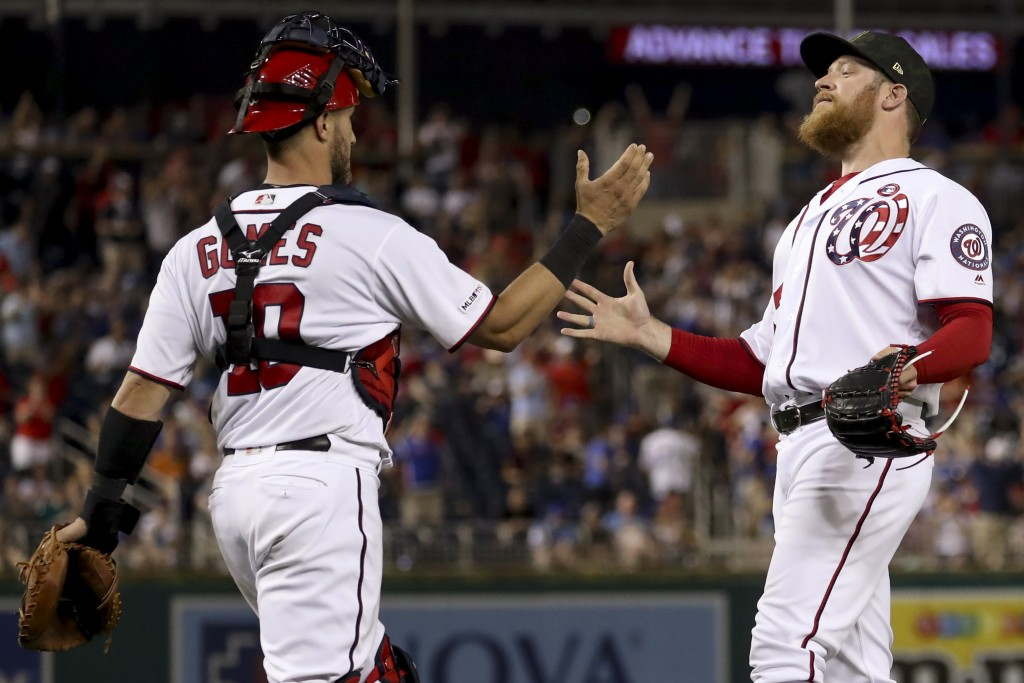 Washington Nationals catcher Yan Gomes (10) and Washington Nationals relief pitcher Sean Doolittle, right, celebrate after the Nationals defeated the ...