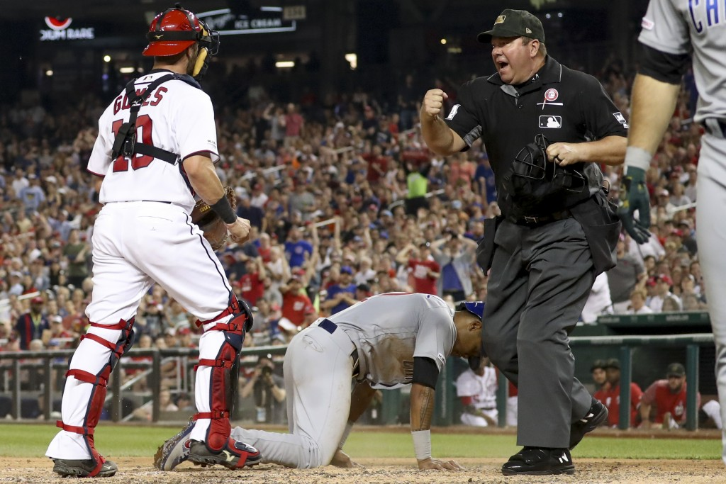 Umpire Sam Holbrook calls out Chicago Cubs' Addison Russell (27) after Washington Nationals catcher Yan Gomes (10) tagged him out after a passed ball ...