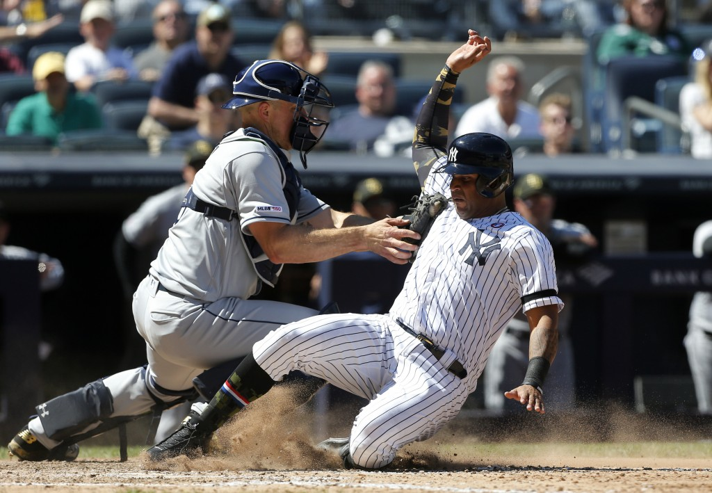 New York Yankees' Aaron Hicks, right, is tagged out at the plate by Tampa Bay Rays catcher Erik Kratz ending the sixth inning of a baseball game, Satu
