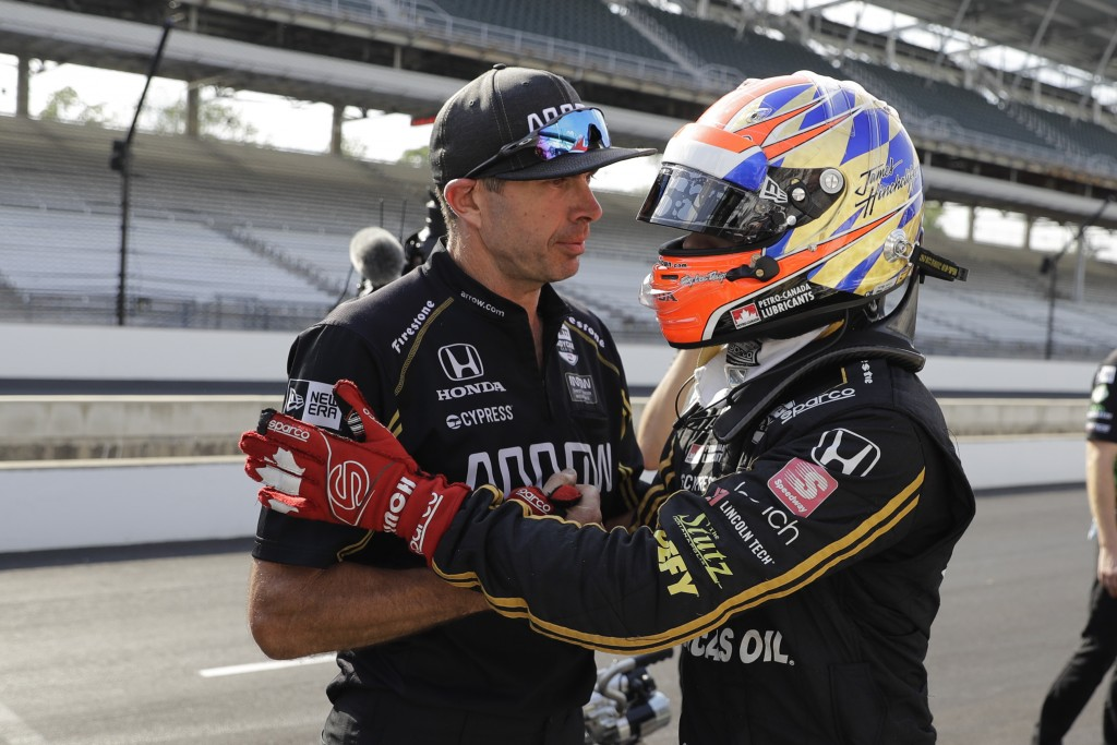 James Hinchcliffe, of Canada, talks with a crew member during qualifications for the Indianapolis 500 IndyCar auto race at Indianapolis Motor Speedway