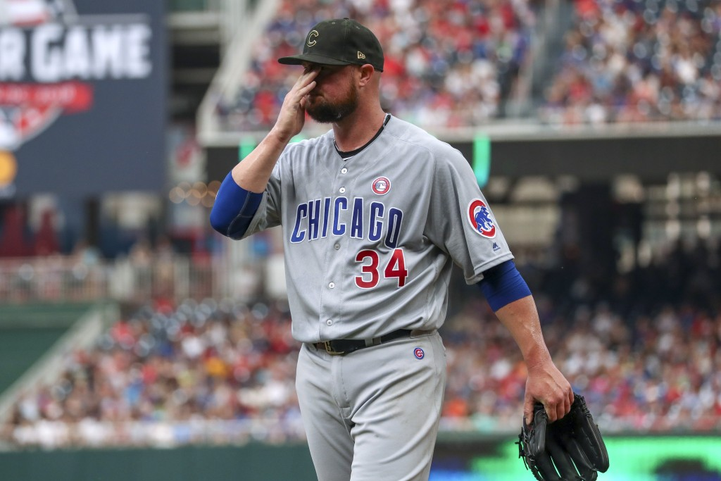 Chicago Cubs starting pitcher Jon Lester wipes his face as he walks off the field at the end of the second inning of the team's baseball game against