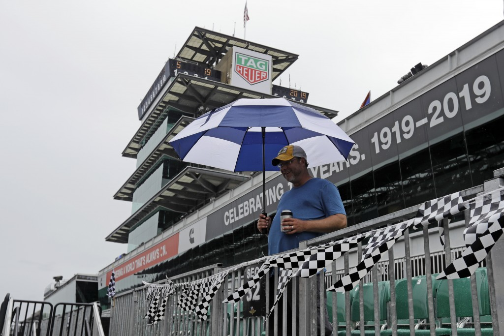 A fan waits as rain delays the final portion of qualifications for the Indianapolis 500 IndyCar auto race at Indianapolis Motor Speedway, Sunday, May