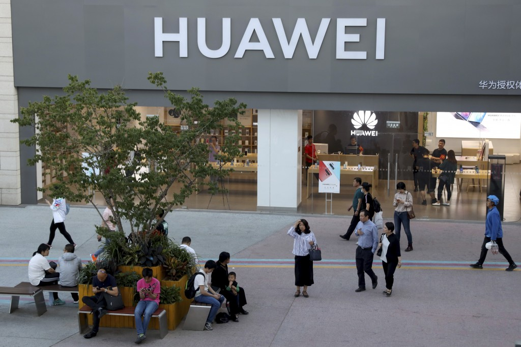 A woman gets her bearing outside a Huawei store in Beijing Monday, May 20, 2019. Google is assuring users of Huawei smartphones the American company's...