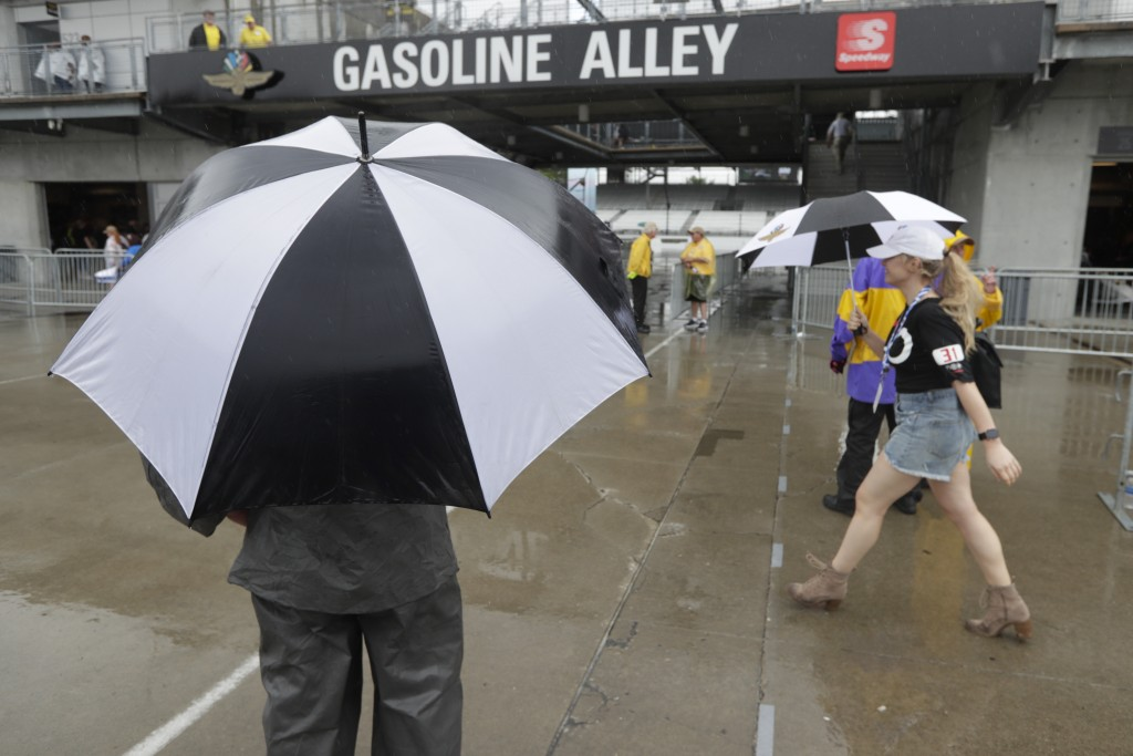 Fans walk past the garage area as rain delays the final portion of qualifications for the Indianapolis 500 IndyCar auto race at Indianapolis Motor Spe
