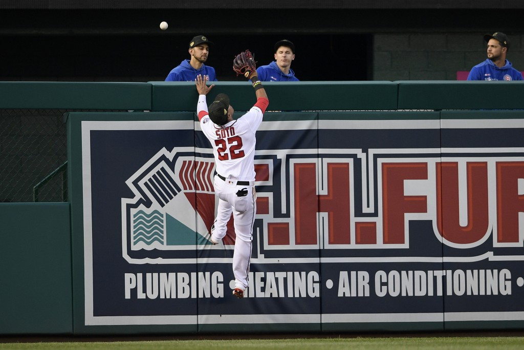 Washington Nationals left fielder Juan Soto (22) leaps for a ball that went for a home run by Chicago Cubs' Anthony Rizzo for a home run during the th...