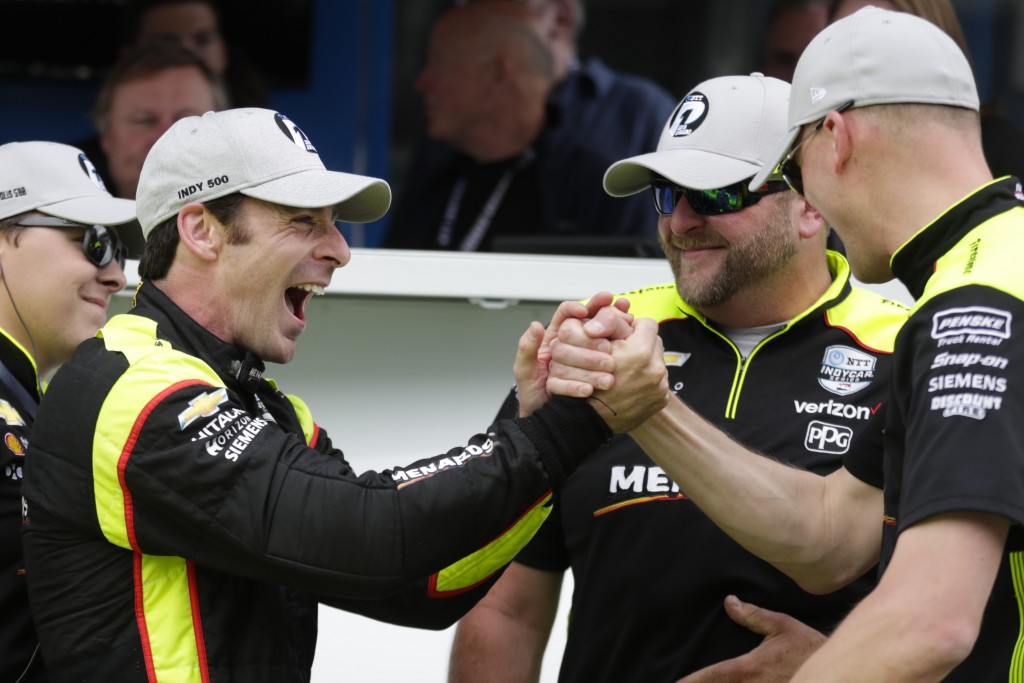 Simon Pagenaud, of France, celebrates with his crew after winning the pole during qualifications for the Indianapolis 500 IndyCar auto race at Indiana...