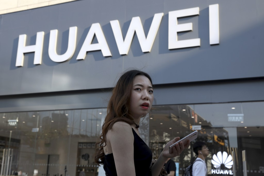 A woman uses a smartphone outside a Huawei store in Beijing Monday, May 20, 2019. Google is assuring users of Huawei smartphones the American company'...