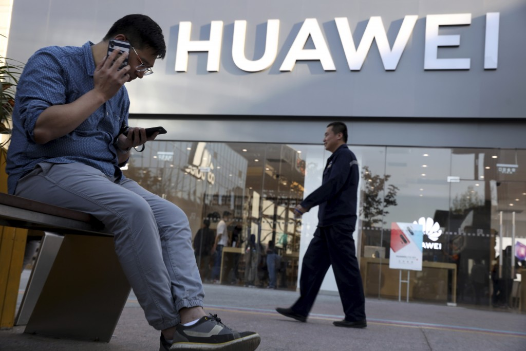 A man uses two smartphones at once outside a Huawei store in Beijing Monday, May 20, 2019. Google is assuring users of Huawei smartphones the American...