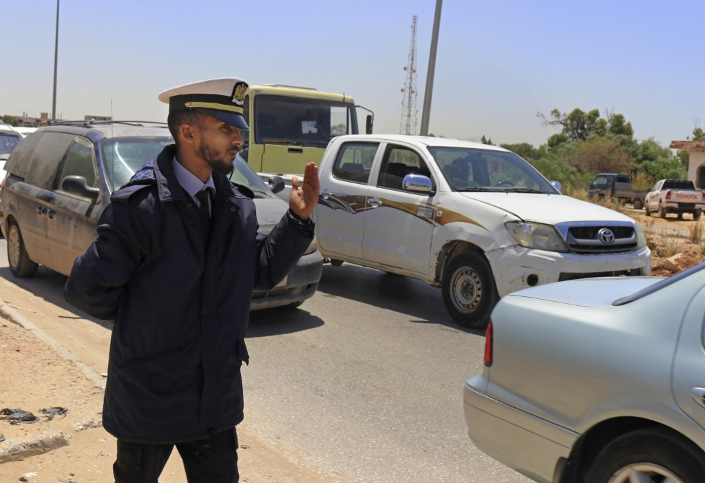 In this May 2, 2019 photo, a police officer waves vehicles through a checkpoint during rush hour in Benghazi, Libya. After years of assassinations, bo