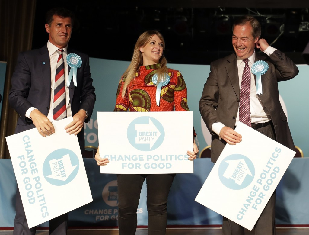 British politician Nigel Farage, right, holds a banner on stage with Brexit Party candidates Robert Rowland, left, and Alexandra Phillips during a Bre