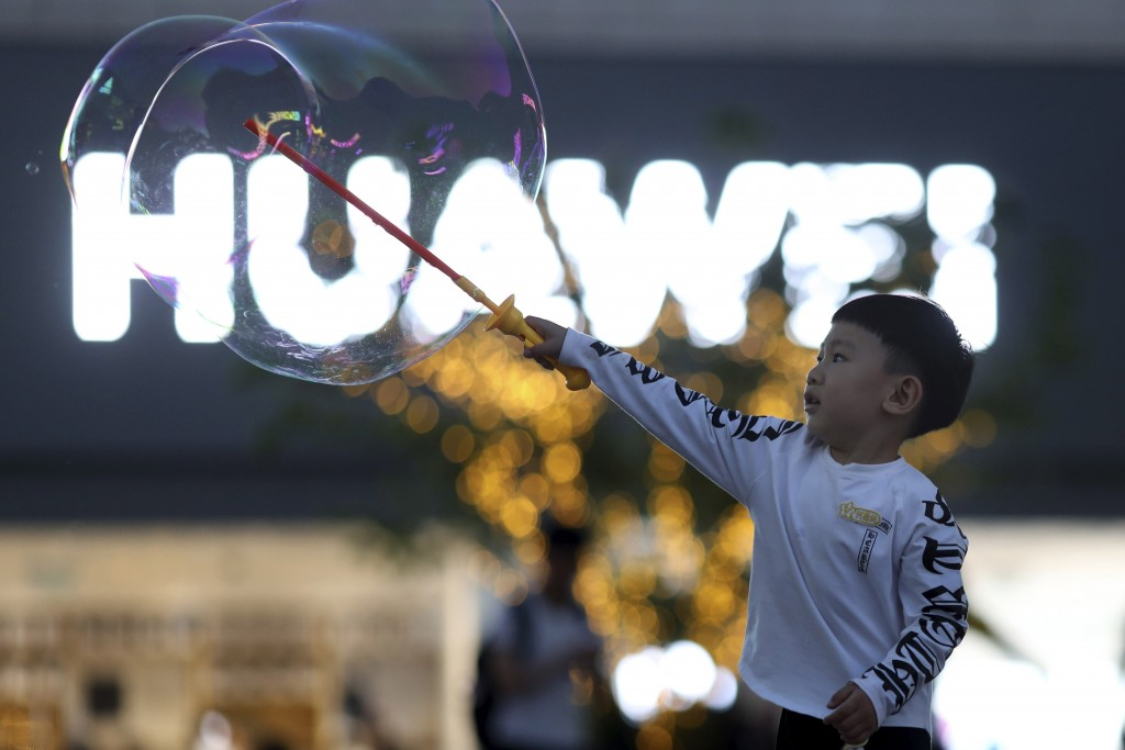 In this Monday, May 20, 2019, file photo, a child plays with bubbles near the logo for tech giant Huawei in Beijing. The Trump administration's sancti