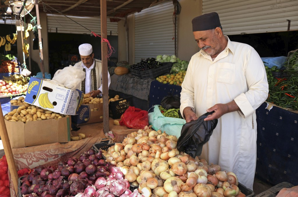 In this April 30, 2019 photo, men shop at a market in Benghazi, Libya. After years of assassinations, bombings and militia firefights, Libya's eastern