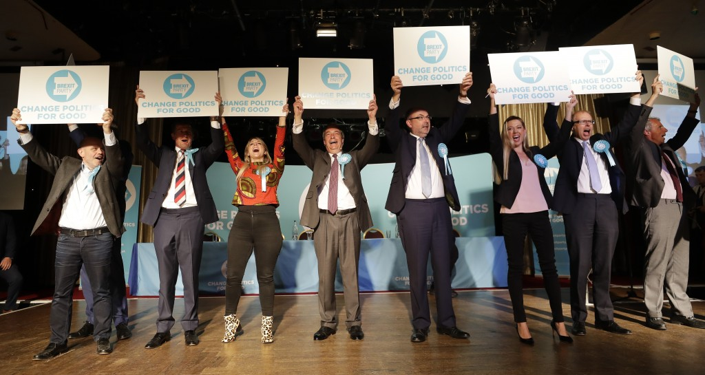 British Politician Nigel Farage, fourth left, holds up a banner alongside Brexit Party candidates on stage during a Brexit Party rally at Lakeside Cou