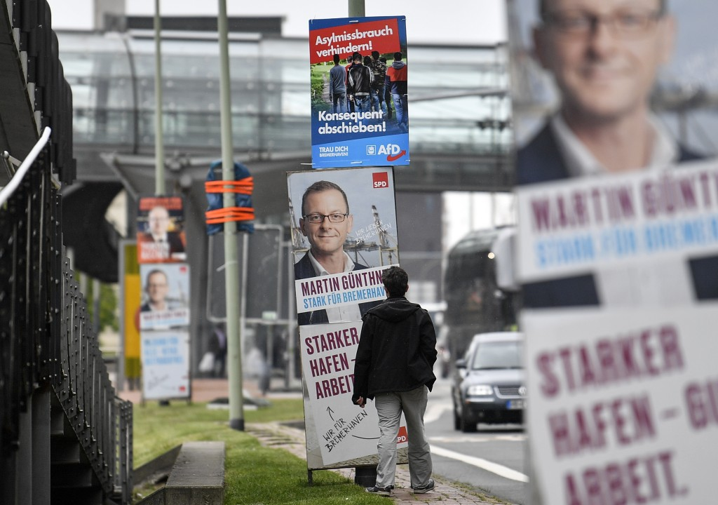 In this Thursday, May 16, 2019 photo, a man stands in fron of posters for the European and state elections of Social Democrats, SPD, and Alternative f